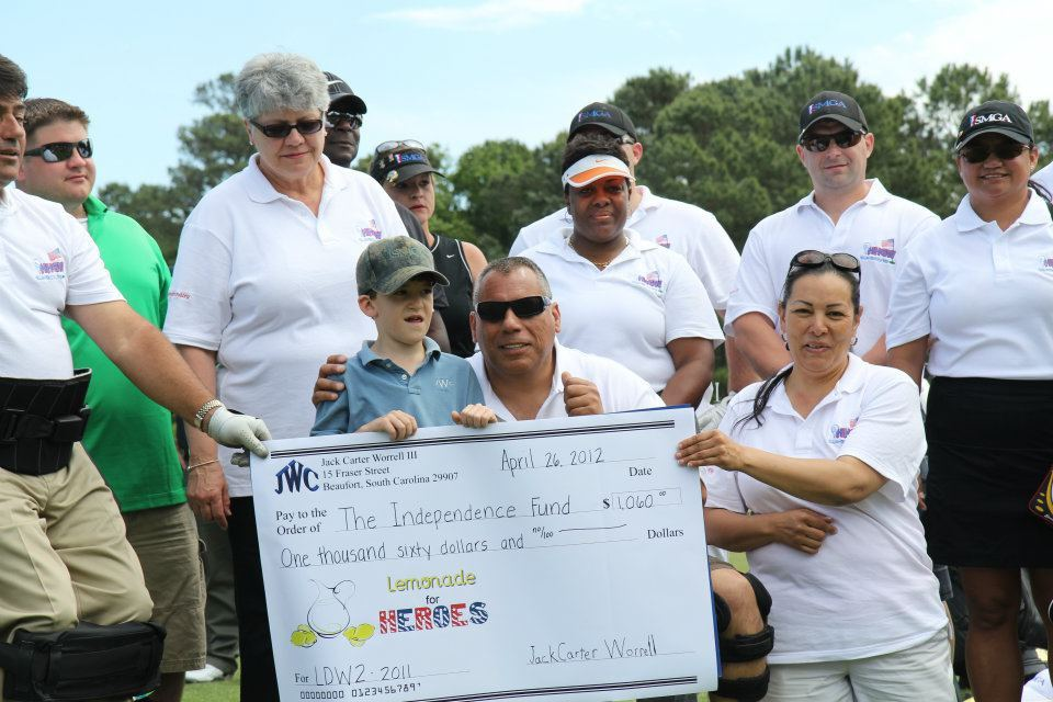 Jack Carter Worrell, 8, presents a check for $1,060 to The Independence Fund before playing golf April 26 with wounded veterans at the Sanctuary Golf Club.