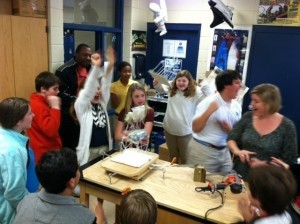 The seventh graders at BA built and tested earthquake towers in Earth Science. This group project was the culmination of the unit on earthquakes. Students were provided with 30 straws, 20 straight pins, and 100 paper clips. They were required to build a 2 story building at least 36 cm tall. The towers had to withstand the shaking with 200g bags of sand on each floor. Pictured: Team of (left to right) Drew Luckey, Sarah Suber, Emily Potter, and John Manos celebrate as their tower withstands more than any other group.