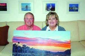 Chris and Teresa Kirk hold one of Chris' photographs at their home on St. Helena Island.