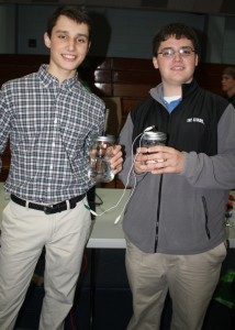 All Beaufort Academy science students in the middle and high schools took part in the BA Science Expo on Thursday, March 21.  During the Expo, students showcased projects going on in their classrooms in addition to special projects done in small teams. Pictured: Sophomore Xavier Westergaard and Senior Bryan Strawn demonstrate their homemade batteries, which they made using copper and iron electrodes.