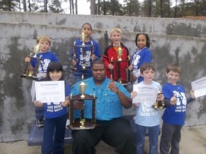 Top row left to right: Whit Suber, who won second place in K-3; Kevin Rogers, who won first place in the K-5 section; Casey Hooganboom, who won first place in the K-3 section; and Kendra Rogers, who won top female. Bottom row, left to right: Sophia Martin; Coach Rogers; Thomas Mazzeo, who won top third grader; and G Simmons.
