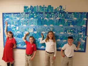 """Artist Pablo Picasso is famous for his """"Blue Period"""" — a difficult time during his life in which he painted almost exclusively in shades of blue.  Holy Trinity students studied Picasso's painting """"Roofs of Barcelona"""" and painted their own """"blue"""" city skylines. Pictured from left is Abby Carte Fourth Grade; William Quade, Third Grade; Morgan Chumney, Third Grade; and CJ Bowman, First Grade."""