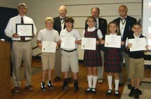 During the program, Chapter Vice President Michael Keyserling presented Rev. Lawrence with the SAR Flag Certificate for the school's patriotic flying of the American Flag, and President Jody Henson and Education Chairman Wayne Cousar presented SAR Certificates of Appreciation to the five student Flag Tenders assigned to daily flag duties and proper etiquette on handling of the flag throughout the year. Pictured at left: Rev. Chad Lawrence, front row Flag Tenders Alex Grabenbauer, Riley Witt, Gabby Warman, Ivy Warman, Gavin Warman; back row Wayne Cousar, Michael Keyserling and Jody Henson.