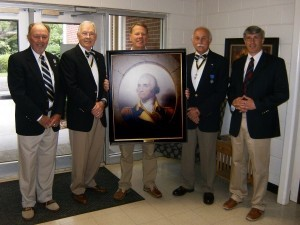 On May 1, the Gov. Paul Hamilton Chapter of the SAR participated in a program at Holy Trinity Classical Christian School in Beaufort, unveiling a new portrait of Gen. George Washington that will be displayed in the school's entrance.  Standing before grades first through fifth, Headmaster Rev. Chad Lawrence welcomed members of the chapter and went on to ask attending students questions concerning the life of Washington. Shown with the Washington portrait are (L-R) compatriots Michael Keyserling, Wayne Cousar, Andy Beall, Jody Henson and school Headmaster Rev. Chad Lawrence.