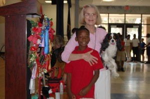 Pam Taub is seen with her Cavalier King Charles Spaniel Chadwick Pickatey and a student from Beaufort Elementary.