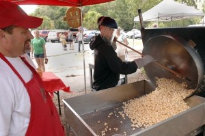 Gerry Pheifer, right,  uses a long, wooden ladle to scoop out the fresh popcorn during Saturday's farmer's market in Port Royal.
