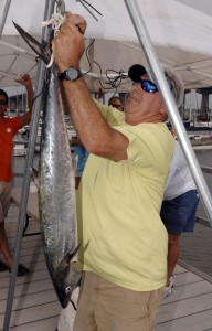 Henri Madlinger weighs the first fish entered in Saturday's Water Festival Off Shore Fishing Tournament. The fish, a 13-pound kink mackerel, was caught by Dean Kennedy.