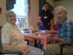Nursing assistant Priscilla Mendoza serving coffee to George Stewart and his wife, Bertha.