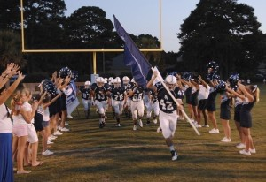 Beaufort Academy's Jake Ingram, center, carries the school's banner to start the Eagles football game against Cathedral Academy last Friday night at BA's Merritt Field.