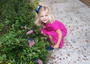 BA PreK-3 student Amelia Mitchell places one of the 3,000 flags.