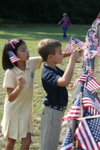 Beaufort Academy third graders Sophia Martin and Alex Roberts put the finishing touches on the flags arranged on the fence around the school.