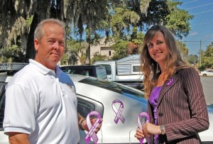 Beaufort County Sheriff P.J. Tanner and CODA Executive Director Kristin Dubrowski place purple ribbon magnets to raise awareness of the campaign against domestic violence.