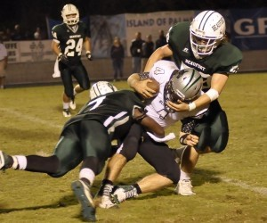 Beaufort High defenders T.J. Watts #7, left, and Eli Glisson #58 wrap up the Bluffton ball carrier last Friday night.