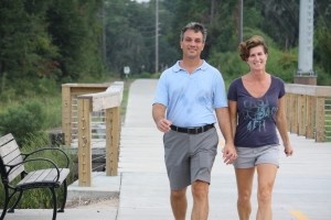 A couple walks along the Spanish Moss Trail between Allison and Depot roads.