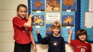 """Holy Trinity Classical Christian School's Art Of The Week was """"The Mulberry Tree"""" by Vincent Van Gogh. Students studied this vibrant piece of art and painted their own trees employing Van Gogh's favorite color combination: yellow and blue. Pictured from left: Morgan Chumney, 6th grade; Levi Qualls, 1st grade; and Kindergartner Hayden Strawn display their handiwork."""