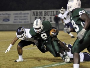 Beaufort High School's Eric Blakely gets tackled by a pair of Burke defenders after gaining extra yards last Friday night.
