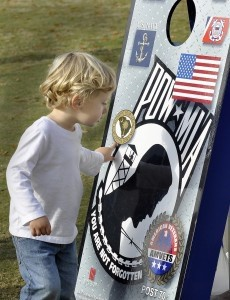 Austin Boyne, 3, isn't old enough to understand the sacrifices veterans make on his behalf as he plays near a display of the corn hole tournament sponsored by the Healing Heroes of the Low Country Fund. Austin was cheering his dad, Douglas Boyne, who was participating in the tournament.