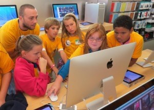 """Beaufort Academy fifth grade students visited the Apple store in Charleston. Students were broken into groups and walked through downtown Charleston to take hundreds of photos on iPods. Back at the store, the students uploaded the photos to desktop Mac computers and generated movies complete with music. Each child received an """"Apple Field Trip"""" T-shirt and a copy of their video on a flash drive. Pictured (left to right): Emmy Wilson, Mason Westerfield, Emma Dillinger, Ansleigh Pingree and Burak Henderson with an Apple representative."""