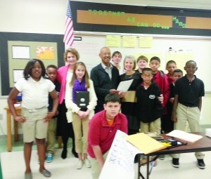 Foundation member Herman Gaither (center) presents a grant to Beaufort Middle School teacher Tricia Fidrych (right) with Principal Carole Ingram (left) and students.