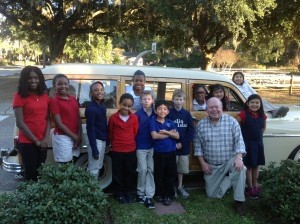 The kids of Thumbs Up pose with Woody in front of his 1949 Plymouth Woody.