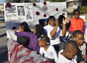 Children wave to the enthusiastic crowd from their float during the annual MLK Day parade on Monday, Jan. 20, 2014.