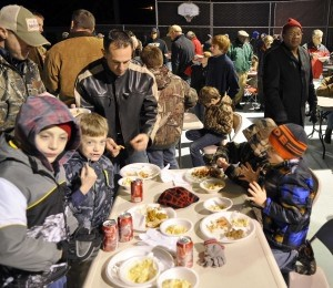 Young boys chow down on the wild game prepared for them.
