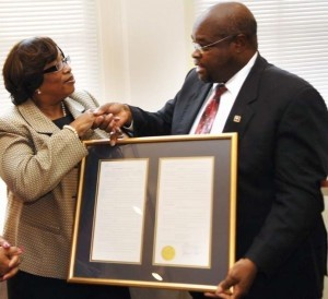 S.C. Representative Kenneth F. Hodges presents Jackie Hollins Lee with concurrent resolutions by the S.C. House of Representatives honoring her father and his contribution to the quest for racial equality 50 years ago.