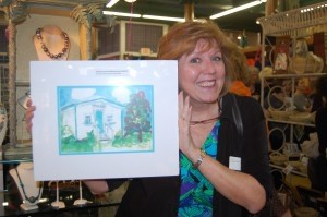 Susan Smith holds up the watercolor print she won from Blue Banjo.