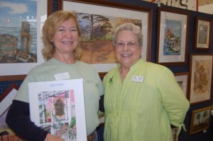 Kimberly Granguist holds a watercolor print of The Beaufort Inn that was donated by artist Ellen Long, at right, who displays and sells her work at Fordham Market.