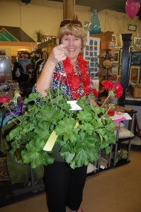 Debbie Barrett holds her giant geranium hanging plant from Mother Earth.