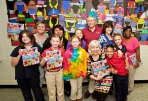 """Lady's Island students and art teacher Stephanie Riedmayer show art on the cover of the book """"Creating Meaning through Literature and the Arts."""" Original student art used for the cover is displayed in the background. Back row from left: Teacher Charlotte Diorio, Principal Marvelle Ulmer, Lisa Ten Eyck, Photographer Eric Smith, Lynda McClain and Jessica Goethie-Bacon. Front row, from left: Students Jenna Derrick, Bailey Herron, Makayla Johnson, Regan Hill and Caitlyn Baughman. Teacher Stephanie Riedmayer is fourth from the left. By Eric Smith of Captured Moments Photography."""