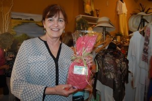 Ginny Bankov excitedly holds up her winning door prize: A bracelet from Greenfish Gallery.