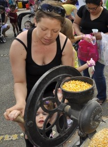Heather Heideman helps her daughter Sophia turn the grinding wheel at the 4-H display last Saturday at the 19th annual KidFest.