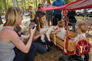 Laura Ballord, left takes the photos of Emily Stuckart holding a baby goat for her twins, Heidi and Lilly, at the petting zoo during KidFest.