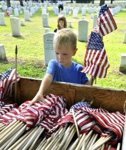 Hunter Graves, 3, son of Diana and Bobby Graves of Beaufort, helps sort out American flags on Thursday, May 22 at Beaufort National Cemetery. The flags were placed at the grave markers at the cemetery.