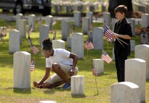 Fifth graders from Lady's Island Middle School help put up some of the American flags in front of each grave last Thursday, May 22 at Beaufort National Cemetery.