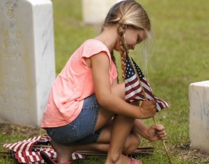 A girl places an American flag at one of the graves last Thursday at Beaufort National Cemetery in preparation for the annual Memorial Day Ceremony at the cemetery.