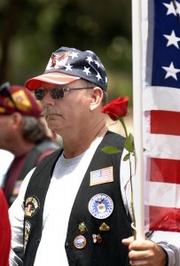 Mike Melton, a Patriot Guard Rider from Charleston, S.C, holds a red rose with his American flag during the Memorial Day ceremony Monday afternoon at the Beaufort National Cemetery.