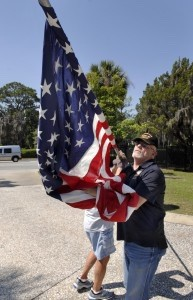 """Volunteer Ken Dennings, right, and George Miller unfurl one of the 50 """"casket"""" flags for the Avenue of Flags on Friday, May 23 at Beaufort National Cemetery. Casket flags are those that draped over the casket of a U.S. veteran. The volunteers were getting the cemetery ready for the annual Memorial Day Ceremony."""