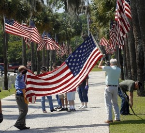 The flags have to been unrolled while the poles are secured to each other. Fifty American flags line the driveway at Beaufort National Cemetery for the annual Memorial Day Ceremony.