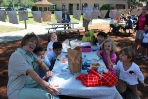 Mrs. Jackie Bauer and a few of her students enjoy an outdoor picnic.
