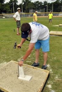 Beaufort Water Festival volunteer Josh Schott adjusts the angle and depth of the iron stake in the sand box before another horseshoe game is played.