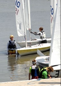 Waiting for the race to start, these young sailors get ready to man their Laser sailboats.