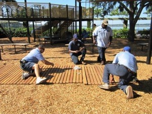 Public Works crews install a wooden walkway to the playground at Henry C. Chambers Waterfront Park.