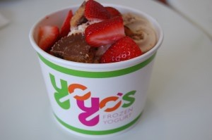 Sea Salt Caramel Frozen Yogurt topped with pecans, Reese's peanut butter cups and strawberries.