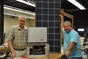TCL industrial technology instructors Rick Eckstrom (left) and Tim Newsome (right) work together on a 3,000 watt inverter and solar panel that will be used in TCL's new solar technology programs.