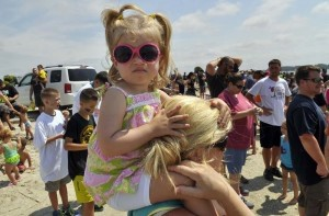 nna Kate Rossengarten, 2, sits on her mother's shoulders to watch the mayhem as shark teeth hunters comb the beach.