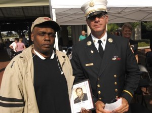 Dwayne Jenkins, left, holds a photo of his cousin Wayne White with Battalion Chief David Simms. White worked in one of the Twin Towers and was killed during the terrorist attack.