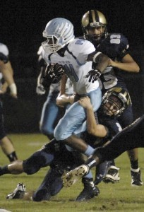 Hilton Head's ball carrier gets pulled down by the Battery Creek High defense during the game at Dolphin Stadium.