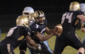 Battery Creek quarterback Raekwon Smalls, center, gets ready to hand off the ball during the first half against Hilton Head High.
